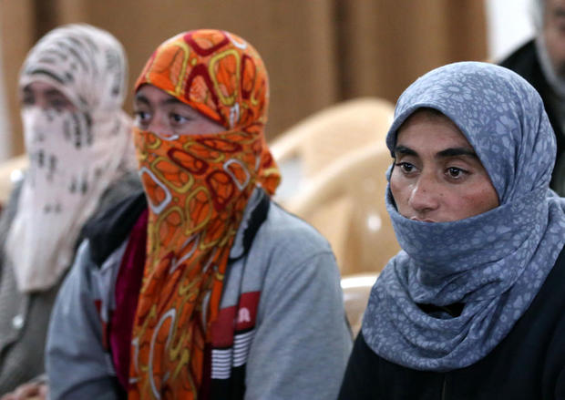 Yazidi women look on at Al-Tun Kopri health centre, located half way between the northern Iraqi city of Kirkuk and Arbil, after they were released with around 200 mostly elderly members of Iraq's Yazidi minority near Kirkuk on January 17, 2015 after being held by the Islamic State jihadist group for more than five months. Medical teams from the Kurdistan Regional Government carried out blood tests and provided emergency care to the group of Yazidis, many of whom looked sick and distraught. Yazidi officials and rights activists say thousands of members of their Kurdish-speaking community are still in captivity.